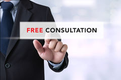 Free Consultation. Businessman touching a touch screen on blurred city background royalty free stock image