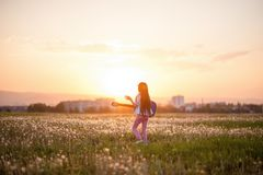 Free creative little girl with long hair playing guitar and singing song outdoor sunset summer field on background of beautiful