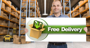 Free delivery, man with sign. A man holding a Free delivery board in a distribution warehouse royalty free stock images