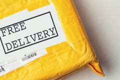 Free delivery text on yellow parcel package or cargo box with product, free logistic shipping and distribution, internet shopping Royalty Free Stock Photos
