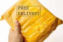 FREE DELIVERY text on yellow parcel package or cargo box with product in male hand, free logistic shipping and distribution Royalty Free Stock Photo