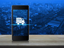 Free delivery truck icon on modern smart phone screen on wooden Royalty Free Stock Photo
