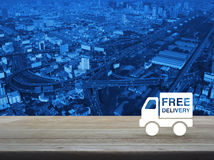 Free delivery truck icon on wooden table over city Stock Image