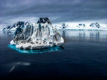 Freed and detached iceberg. Cause of the global warming, a huge block of iceberg detached from the Iceland floating on the Arctic ocean followed by a blue and