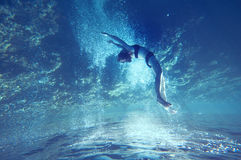 Free dive. Freediving girl with air bubbles and corals, and water surface Stock Photos