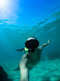 Free diver coming to surface. Young man snorkeling in the Pacific Ocean Stock Photography