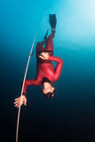 Free diver. Descending along the rope in the depth Stock Images