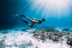 Free diver glides over sandy sea with fins. stock photography