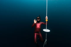Free divers showing OK sign. Hanging on a depth by the end of training line Royalty Free Stock Image