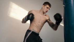 Strong caucasian man boxing using punch sake. Free fighter with tattoo training punching bag, slow motion stock video
