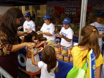 Free Food for the Family. Photo of mother and her children receiving a free samples of goya food at the mount pleasant latino festival on 9/27/09.  Goya is one Royalty Free Stock Images