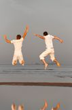 Free friends. Two friends is jumping at morning beach Royalty Free Stock Images