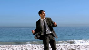 Free happy businessman dancing on the beach. In slow motion stock video