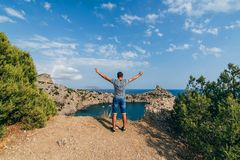 Free happy male traveler with arms raised. To the sky in the rest is on top of a mountain Stock Photo