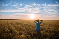 Free Happy Woman Enjoying Nature and Freedom Outdoor. Woman with arms outstretched in a wheat field in sunset. Stock Photo
