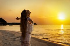Beautiful, young woman in white dress embracing the golden sunset Stock Photography