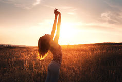 Free happy woman raising arms at sunset in the field Royalty Free Stock Image