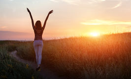 Free happy woman raising arms at sunset in the field. Free happy young woman raising arms at sunset in the field in summer. Background Royalty Free Stock Images