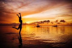 Free happy woman raising arms watching the sun stock photo