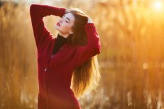 Free happy young woman. Beautiful female with long healthy hair enjoying sun light in park at sunset. Spring, autumn Royalty Free Stock Image