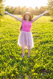 Free happy young woman raising arms watching the sun in the background at sunrise Royalty Free Stock Photos