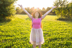 Free happy young woman raising arms watching the sun in the background at sunrise Royalty Free Stock Photo