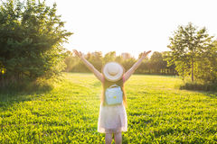 Free happy young woman raising arms watching the sun in the background at sunrise Royalty Free Stock Images
