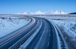 Free highway in morning time and snowed mountains on horizon Stock Photos