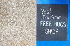 Free hugs sign on shop wall written in chalk on black board against neutral and blue background royalty free stock images