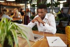 Free lance africane che lavorano al ristorante con il computer portatile Fotografie Stock