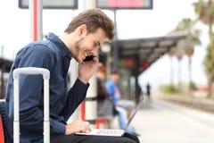 Free lance che lavorano con un computer portatile e un telefono in una stazione ferroviaria Immagini Stock Libere da Diritti