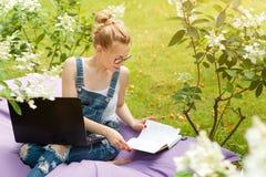Free lance che lavorano nel giardino Scrivendo, praticante il surfing in Internet Giovane donna che si rilassa e che si diverte n fotografie stock