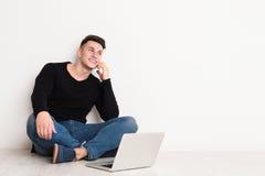 Free lance del giovane in casuale con il computer portatile che parlano sul telefono cellulare Fotografia Stock Libera da Diritti