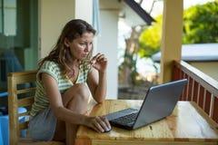 Free lance della donna che si siedono con un computer portatile sulla veranda del bungalow Immagine Stock