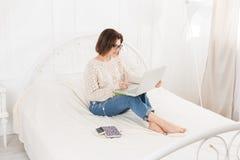 Free lance della giovane donna con il computer portatile a letto, alta chiave Immagini Stock