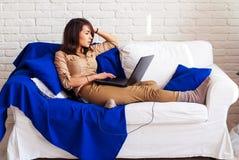 Free lance della ragazza che lavorano a casa per un computer portatile La ragazza sullo strato con un computer portatile Una stud Immagini Stock