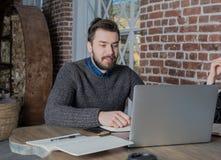 In free lance esperte del giovane tipo barbuto dei pantaloni a vita bassa che lavorano al computer portatile, sedentesi nello spa Immagini Stock
