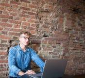 In free lance esperte dell'uomo allegro dei pantaloni a vita bassa che lavorano al computer portatile nell'interno moderno Fotografia Stock