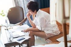 Free lance femminili asiatiche che si siedono sullo strato che pensa & che lavora al computer portatile a casa immagine stock libera da diritti
