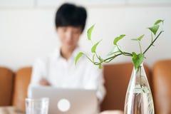 Free lance femminili asiatiche che si siedono sullo strato che pensa & che lavora al computer portatile a casa fotografie stock