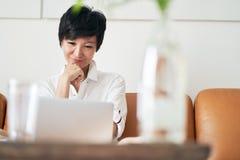 Free lance femminili asiatiche che si siedono sullo strato che sorride & che lavora al computer portatile a casa fotografia stock