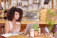 Free lance femminili che lavorano in una caffetteria sul suo computer portatile Fotografia Stock Libera da Diritti