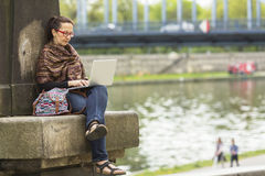 Free lance femminili che si siedono all'aperto con il computer portatile Immagine Stock
