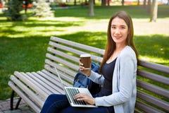 Free lance motivate nel parco Ragazza sorridente su un banco, su un caffè bevente e su un lavoro con il computer portatile Fotografia Stock Libera da Diritti