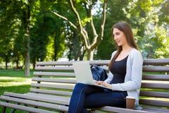 Free lance motivate nel parco Ragazza su un banco, su un caffè bevente e su un lavoro con il computer portatile Immagini Stock