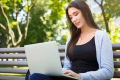 Free lance motivate nel parco Ragazza su un banco, sorridente e lavorante con il computer portatile Fotografie Stock Libere da Diritti