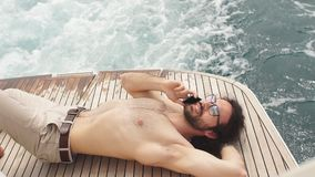 Free life. Portrait of the handsome and rich man sunbathing. Shot from marine private yacht. Man relaxing under the sun, lying on a wooden deck of the boat at stock video footage
