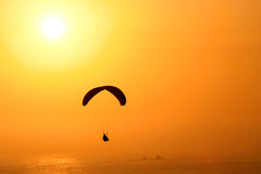 Free like a bird. Paraglider infront of an amazing sunset in southamerica. Very warm colors and a bit of motion blur in the ocean Royalty Free Stock Image