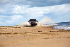Free offroad driving. Big four-wheel car driving on sandy sea coast in water splashes Royalty Free Stock Photography