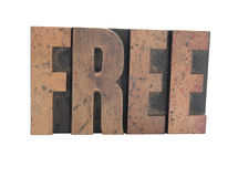 'FREE' in old wood type. Old, ink-stained wood letterpress type spells out the word 'FREE' in all caps, isolated on white Stock Image